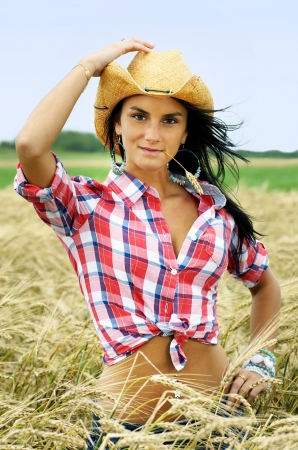 Beautiful friendly brunette cowgirl with cowboy hat chewing straw in a wheat field. photo