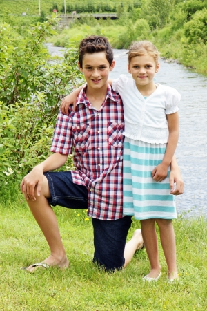 Young brother and sister enjoying summer at the cottage near a river in Quebec, Canada. photo