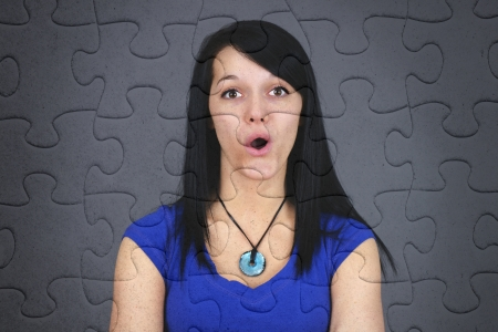 Fun concept of very surprised or puzzled young brown hair woman on jogsaw puzzle, great texture and details of the pieces. photo