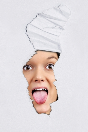 Fun ripped textured paper background with pretty young woman pulling tongue behind. photo