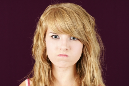 Mad young blond teenage girl, funny face concept.