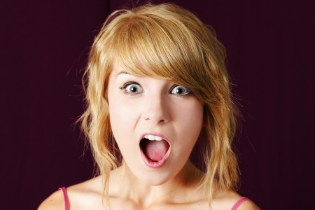 Very surprised or shocked young blond teenager girl making funny face, with eyes and mouth wide open, studio shot.