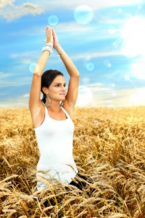 Beautiful healthy young woman connecting or communing with nature by doing yoga and meditation at dawn in a ripe wheat field.HDR rendering with light effects. photo