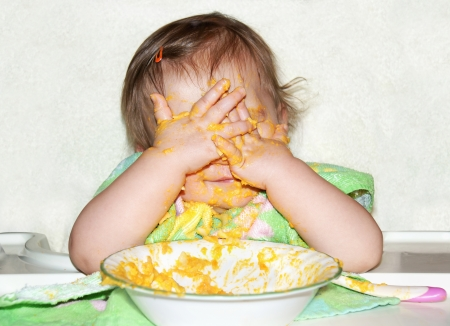 Funny baby with food covered face by putting her hands over her eyes to play picaboo during mealtime, wrong time to do so. photo