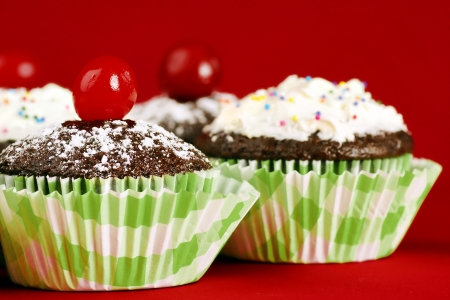 Delicious chocolate cupcakes topped with powdered sugar and maraschino cherry, other desserts with frosting and candies at the back, over red, stacked focus.