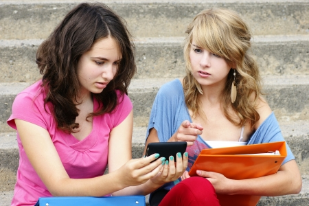 cyber bullying: Cyber or online bullying concept with two young women students or teenager girls shocked at the text they are reading on their cell phone, perfect for awareness.