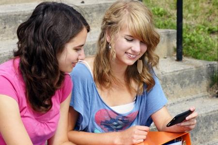 Dos estudiantes adolescentes j�venes utilizando su tel�fono celular y la risa, ideal para la creaci�n de redes, las redes sociales y los gustos. Foto de archivo - 14949418