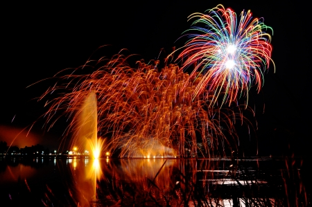 Impressive, bright and colorful fireworks over a lake with lighten water fountain, great celebration background. photo