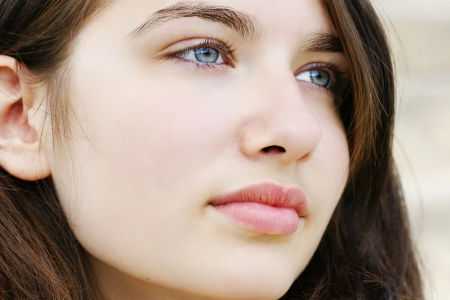 Portrait of s beautiful hopeful or pensive young woman with fair skin and light blue and green eyes, simple and natural. photo