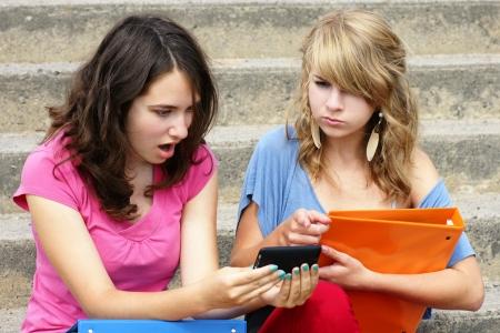 사이버 또는 그들이 인식에 대한 완벽한, 자신의 휴대 전화에 읽고있는 텍스트에 충격을 두 젊은 여성 학생 또는 십대 소녀와 온라인 괴롭힘의 개념입 스톡 콘텐츠