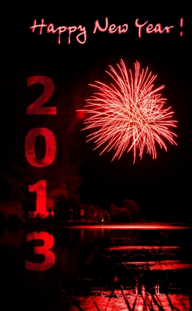 Beautiful 2013 red firework over a lake celebration background or new years eve card.