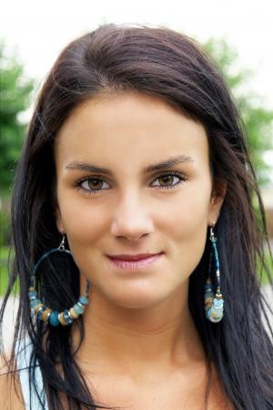 Portret van een mooie brunette jonge vrouw met meisje naast de deur kijken