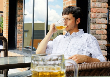 excess: Young man or student drinking beer from glass bock while sitting outside at pub or restaurant terrace.  Stock Photo