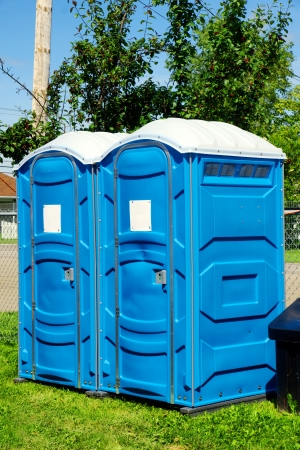 latrine: Two portable toilet or loo in blue plastic at a park public event or concert, with white sign on door ready for text. Stock Photo