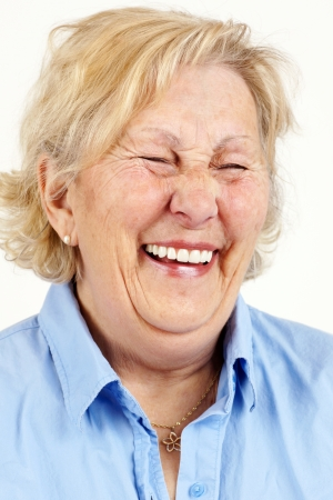 hysterical: Portrait of a blond senior woman laughing hysterically or giggling.