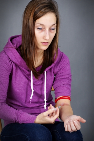 junkie: Young woman junkie, getting high injecting drugs, like heroin, with seringe in her arm; great for substance abuse and narcotics related social issues. Stock Photo