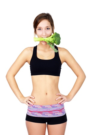 'flat stomach': Humorous nutrition concept: slim, healthy and fit young woman with broccoli stalk in her mouth.