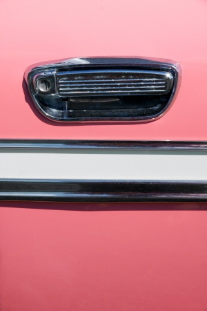 handle bars: Close up on the handle and chrome decoration on an old pink vintage car; great background.