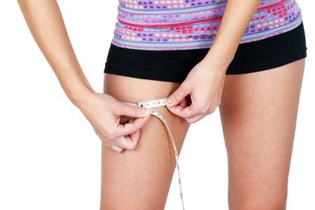 figure out: Thin, fit or anorexic young woman measuring her thigh, perfect for weigth related issues: nutrition, anorexia, sports and others.