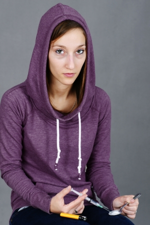 Young woman junkie, getting ready to inject drugs, like heroin, with syringe photo