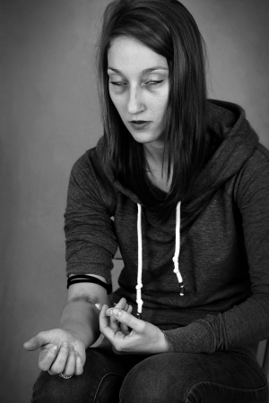 methamphetamine: Dramatic black and white portrait of a young woman junkie, getting high injecting drugs