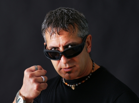 tough: Angry tough guy or criminal with dark biker sun glasses staring at viewer and threatenig him with his closed fist.