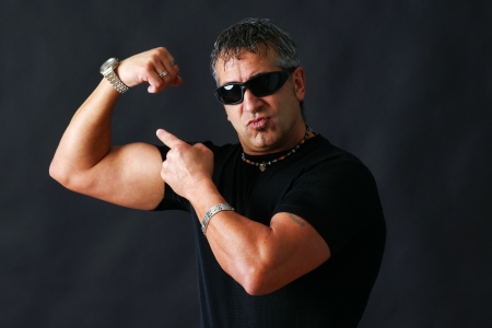 intimidation: Tough guy with dark glasses, could be criminal, showing his big bicep muscle has an intimidation tactik, studio shot over black.