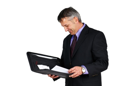 Man in suit and tie, holding paperwork looking at it and smiling, can be boss or management employee. photo