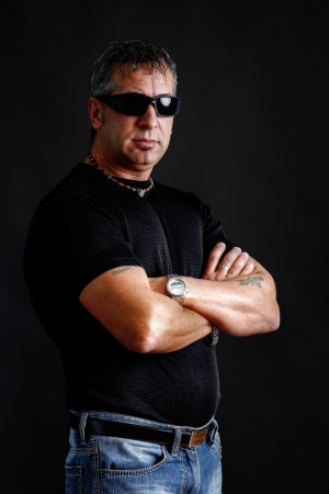 somber: Somber tough guy with tatoos and black sunglasses, arms crossed, looking at camera, studio shot over black.
