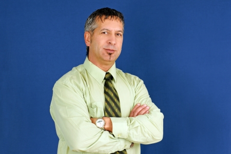 Middle age caucasian business man, can be boss, manager or other employee, arms crossed with little smile on his lips, studio shot over blue background.