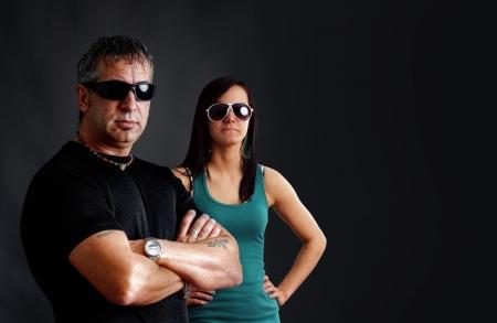pandilleros: Pareja Biker: tipo duro con tatuajes y gafas de sol negras, con los brazos cruzados, mirando a la cámara con una mujer joven y bonita morena, tiro del estudio sobre negro.