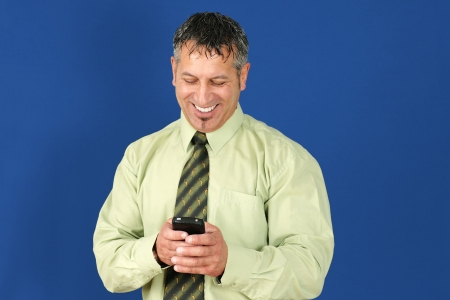 ordinary: Happy and smiling middle aged man or businessman, with salt and pepper hair, reading or texting message on his smart cell phone or mobile.