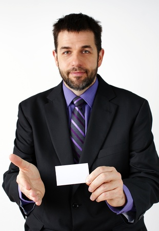 Middle aged man smiling while presenting his hand to meet a colleague while holding a blank business card, great business concept. photo