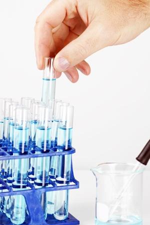 productos quimicos: Químico o otro científico e investigador recoger un tubo de ensayo lleno de química azul o fondo líquido, gran ciencia.