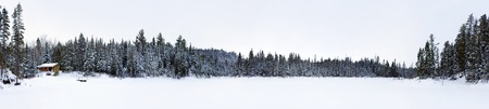 XXXL panorama of a log cabin by a frozen lake, with the forest full of coniferous trees covered in thick snow, low light conditions typical of Northern climates, great season landscape. photo