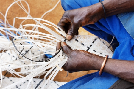 Hands of a black african worker, recovering plastic by weaving long strands to make decorative and strong belts to be reused as different objects.