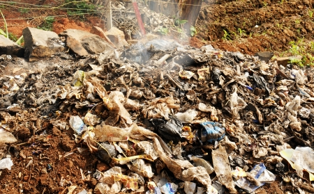 waste management: Pile of rubbish, garbage and various products, including lots of plastic, being burnt as a form of waste management in a third world country. Stock Photo