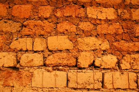 Wall of a house in red clay, earth or soil bricks, great texture background, poverty, developing or tropical country concept. photo