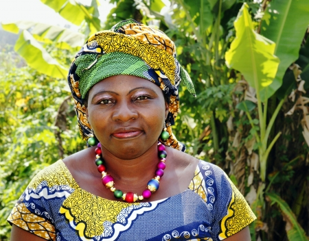Portrait of a beautiful middle-aged black African woman, wearing traditional clothing or boubou with scarf in bold graphic pattern.