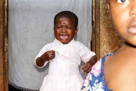 Caught on the fly: little black African baby girl, crying loudly, with bigger sister in the foreground; focus on crying toddler; candid, natural and unstaged portraits.
