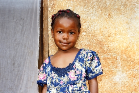 Portrait of a cute and sweet little black African girl, smiling but looking a bit shy, posing in front of her house.