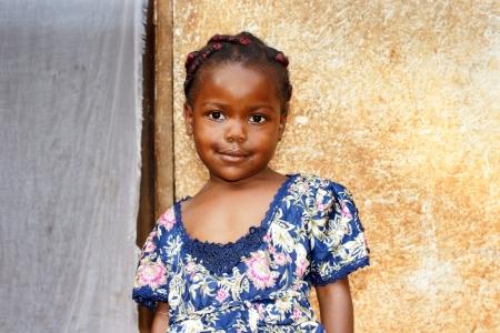 pauvre: Portrait d'un mignon et doux petite fille africaine noire, mais en regardant sourire un peu timide, posant devant sa maison.