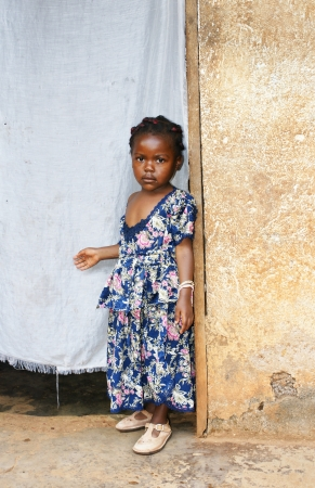 Cute but serious little black African girl in pink sunday dress next to her home door made of fabric; third world or developing country concept.