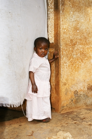 developing country: Cute but sad little black African girl in pink sunday dress next to her home door made of fabric; third world or developing country concept.