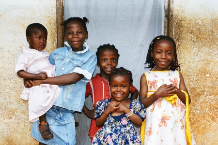 poor children: Real candid family photo of five cute and sweet black African sisters or girls, all smiling in their sunday dress, perfect for developing country and third world population issues.