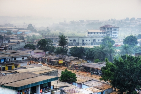 Big African city at dawn with typical tin roofs and people already out in the streets.