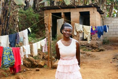 mujeres africanas: Joven y bella mujer africana en el patio con tendedero