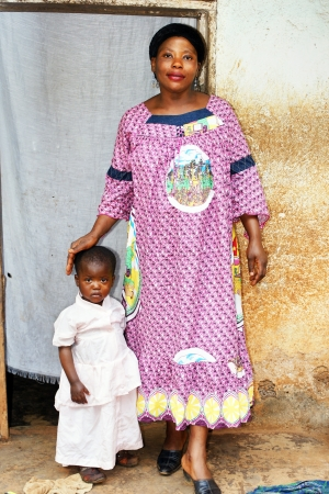 Pregnant black African motherand baby girl in front of their house photo