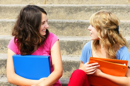 two people talking: Teenage girlfriends talking and laughing at school