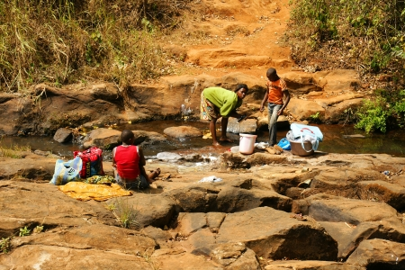 rock creek: AFRICA,CAMEROON, FONGO-TONGO - JANUARY 20  African young woman with men washing clothes in a river  Fresh water is not available in most rural household in Cameroon
